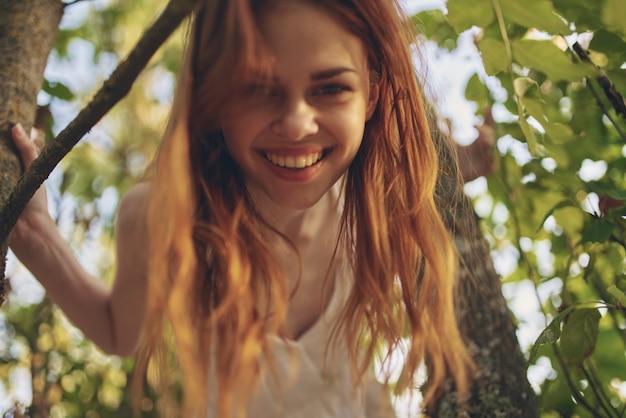 Roodharige vrouw in het bos in de buurt van de boom natuur zomer