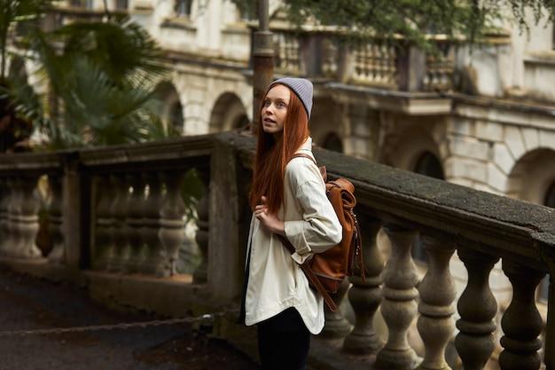 Roodharige vrouw in jas op zoek naar prachtige historische plek kijkend naar de kant van attracties jonge k...