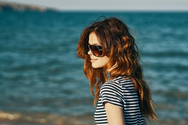 Roodharige vrouw in zonnebril op het strand in de buurt van de blauwe zee en de bergen op de achtergrond. hoge kwaliteit foto