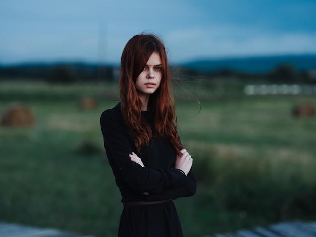 Roodharige vrouw in zwarte jurk in de natuur buiten