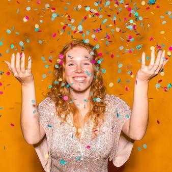 Roodharige vrouw kleurrijke confetti gooien