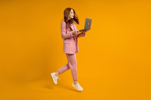 Roodharige vrouw loopt sprong typende laptop met een elegant roze pak geïsoleerd op een gele achtergrond in de studio, schiet op. zijaanzicht portret van dame die op laptop werkt. kopieer ruimte voor advertentie.