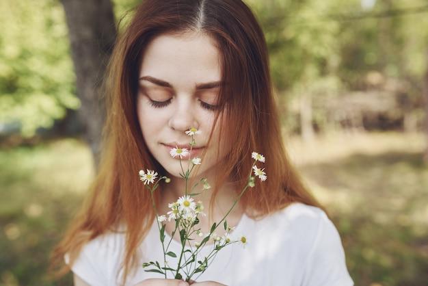 Roodharige vrouw met boeket bloemen natuur bomen zomervakantie. hoge kwaliteit foto