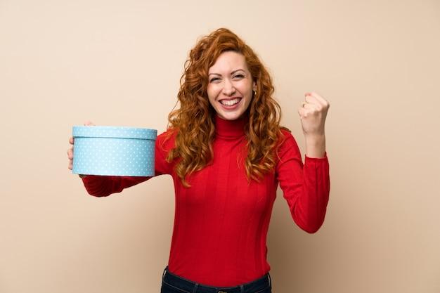 Roodharige vrouw met coltrui trui houden geschenkdoos