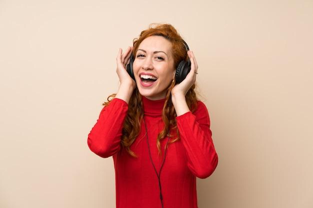 Roodharige vrouw met coltrui trui luisteren naar muziek met een koptelefoon
