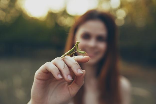 Roodharige vrouw met een bidsprinkhaan in de hand wilde natuur. hoge kwaliteit foto