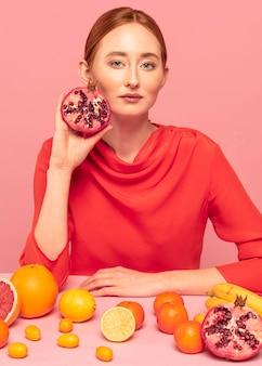 Roodharige vrouw met een granaatappel