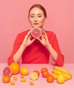 Roodharige vrouw met een grapefruit