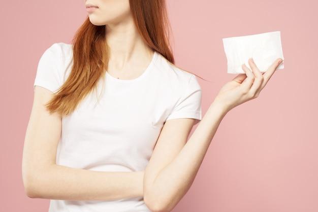 Roodharige vrouw met een kussentje in haar hand en in een wit t-shirt op een roze achtergrond