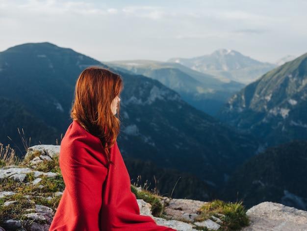 Roodharige vrouw met een plaid op haar schouders rusten in de bergen.