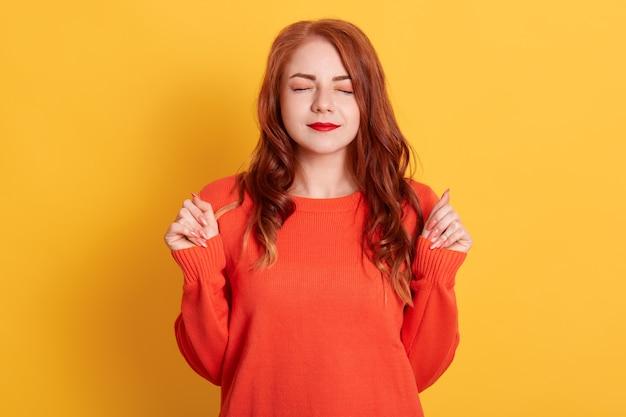 Roodharige vrouw met gesloten ogen gebalde vuisten, wens maken, oranje trui dragen, geïsoleerd staan