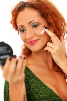 Roodharige vrouw met gezichtscrème