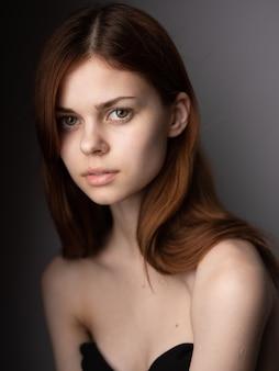 Roodharige vrouw met kale schouders portret close-up donker model.