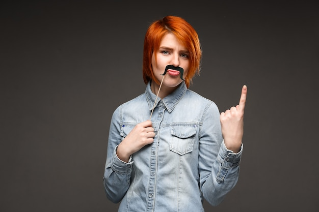 Roodharige vrouw met nep snor grimassen