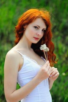 Roodharige vrouw met paardebloemen.