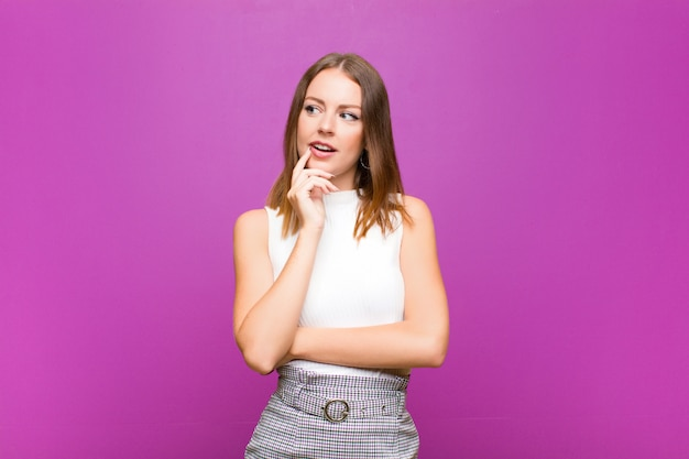 Roodharige vrouw met verbaasde, nerveuze, bezorgde of bange blik, opzij kijkend naar kopie ruimte op paarse muur