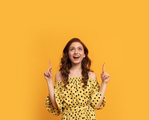 Roodharige vrouw met verrassingsgezicht naar boven gericht in gele zomerjurk poseren op geel