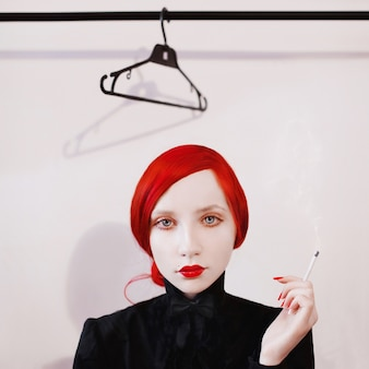 Roodharige vrouw rookt een sigaret op een witte achtergrond meisje in een zwart shirt en vlinderdas met rode lippen en nagels met bleke huid, rook van sigaretten
