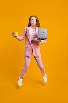 Roodharige vrouw springen gaan met behulp van laptop webproject geïsoleerd op gele achtergrond in studio holdi...