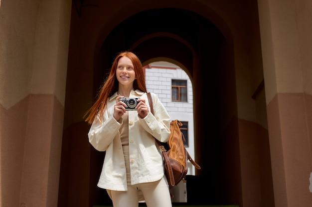 Roodharige vrouw toerist lopen op straat in de europese oude stad met behulp van camera glimlachend jonge blanke la...