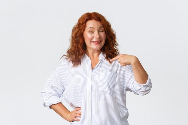 Roodharige vrouw van middelbare leeftijd wijzend op zichzelf