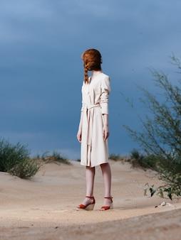 Roodharige vrouw van volle lengte met een vlecht op haar gezicht in een zonnejurk en rode schoenen