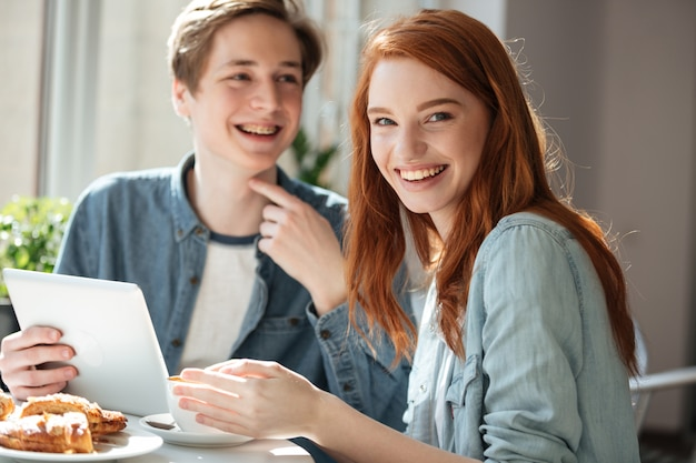 Roodharige vrouwelijke student die camera in koffie kijken
