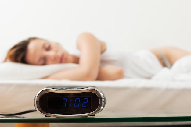 Roodharige vrouwenslaap in bed thuis