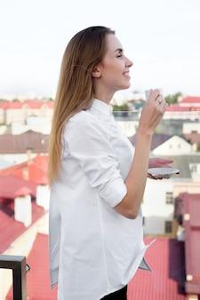 Roodharige wit meisje in wit overhemd koffie drinken