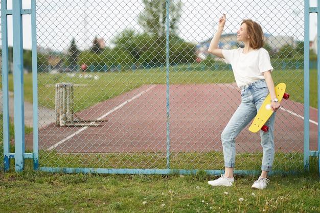 Roodharige wit meisje met skateboard in de buurt van hek