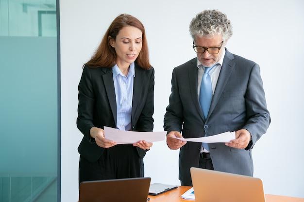 Roodharige zakenvrouw project uit te leggen, papier te houden en staan in de buurt van tafel met laptops