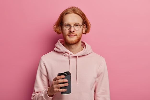 Roodharige zelfverzekerde foxy man heeft koffiepauze, geniet van cafeïnedrank na lezingen