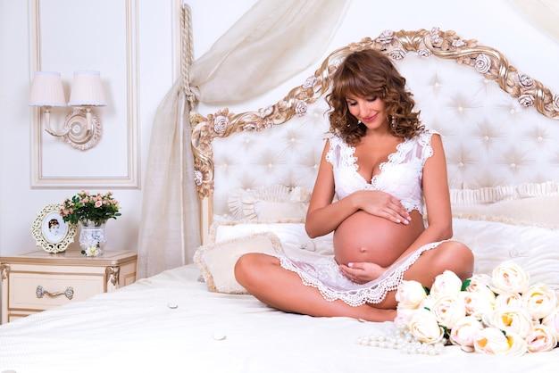 Roodharige zwangere meid zit op bed in lotushouding en knuffelt buik