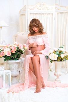 Roodharige zwangere vrouw zit op stoel en kijkt liefdevol naar buik belly
