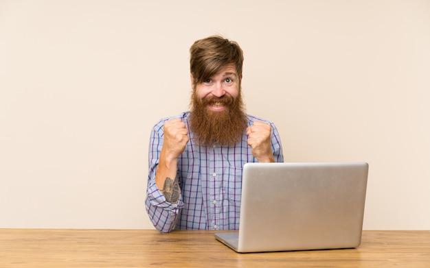 Roodharigeman met lange baard in een tafel met een laptop die een overwinning viert