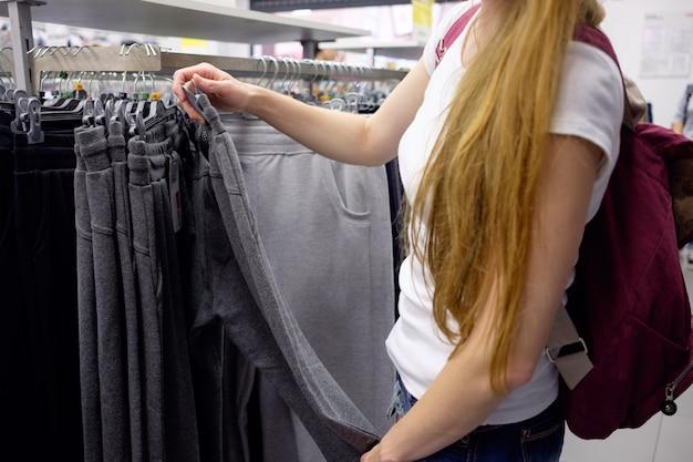 Roodharigemeisje die doeken in sportkledingswinkel kiezen