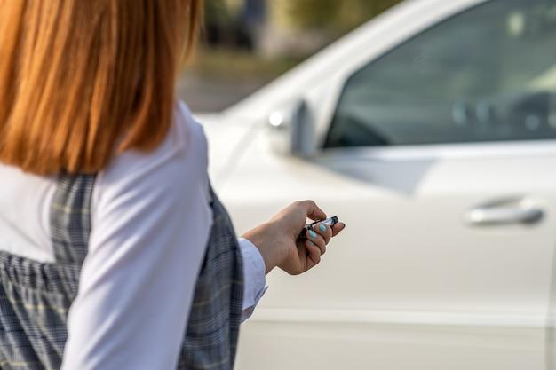 Roodharigemeisje die een auto met draadloze sleutel ontgrendelen.
