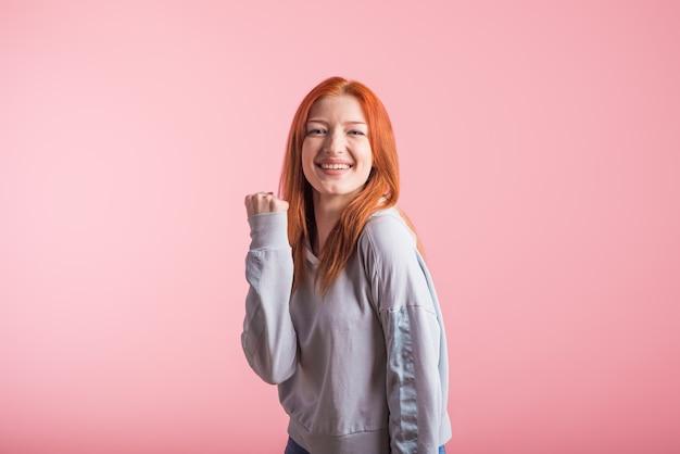 Roodharigemeisje die winnaargebaar in studio op roze achtergrond tonen