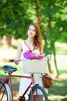 Roodharigemeisje met retro fiets in het park.