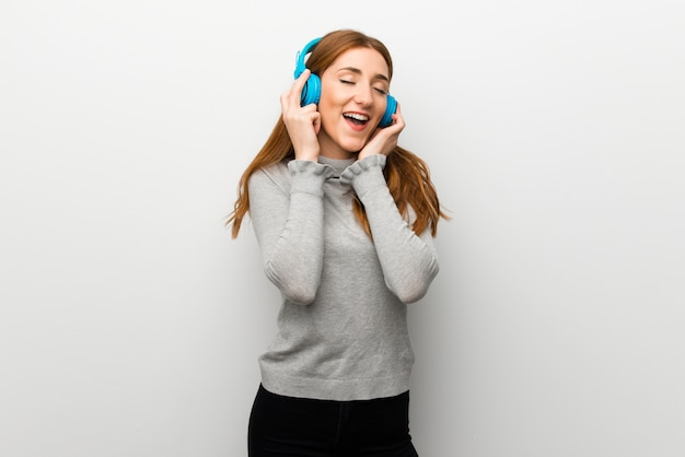 Roodharigemeisje over witte muur die aan muziek met hoofdtelefoons luisteren