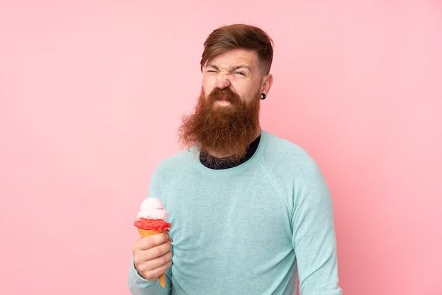 Roodharigemens die met lange baard een cornetroomijs over geïsoleerde roze muur houden die twijfelgebaar maken terwijl het opheffen van de schouders Premium Foto