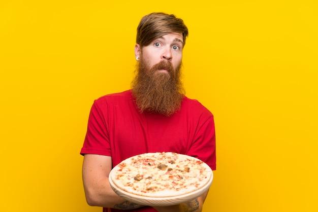 Roodharigemens die met lange baard een pizza over geïsoleerde gele muur houden die twijfelgebaar maken terwijl de schouders opheffen