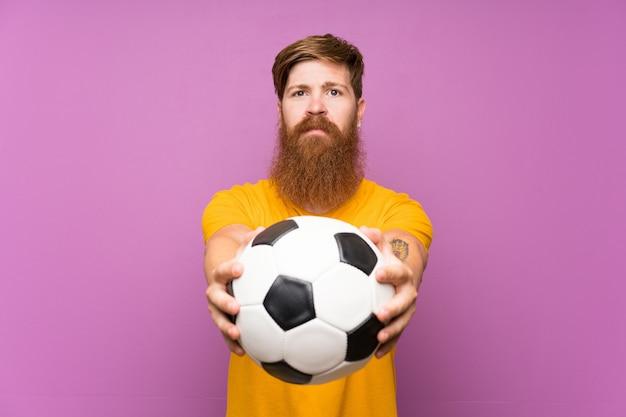 Roodharigemens die met lange baard een voetbalbal over geïsoleerde purpere muur houden