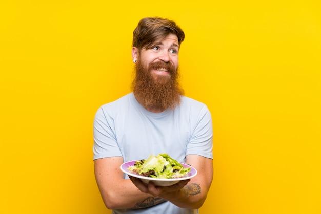 Roodharigemens die met lange baard en met salade over geïsoleerde gele muur omhoog terwijl het glimlachen kijken