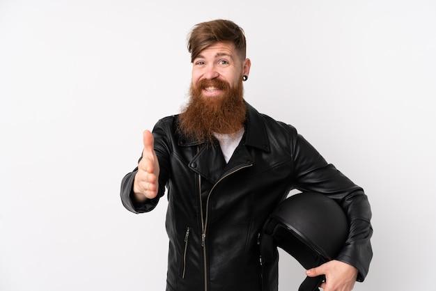 Roodharigemens met lange baard die een motorfietshelm over wit muurhandenschudden houden na veel