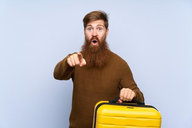 Roodharigemens met lange baard die een verrast koffer houden en voorzijde richten