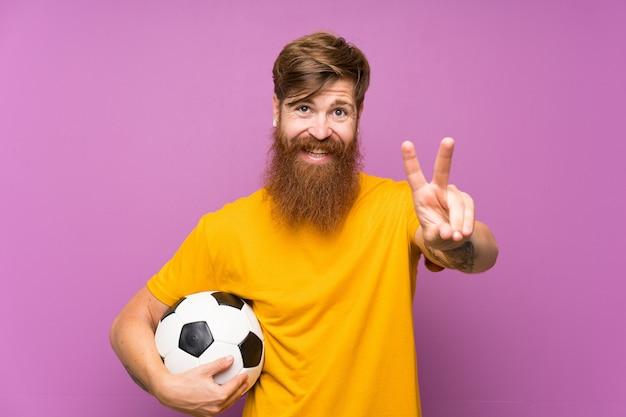 Roodharigemens met lange baard die een voetbalbal over geïsoleerde purpere muur houden die en overwinningsteken glimlachen tonen