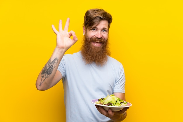 Roodharigemens met lange baard en met salade over geïsoleerde gele muur die ok teken met vingers tonen