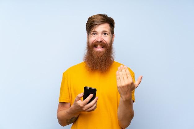 Roodharigemens met lange baard met mobiel over geïsoleerde blauwe muur die met hand uitnodigen te komen. blij dat je bent gekomen