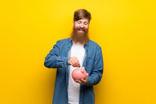 Roodharigemens met lange baard over geïsoleerde gele muur die een grote spaarpot houden